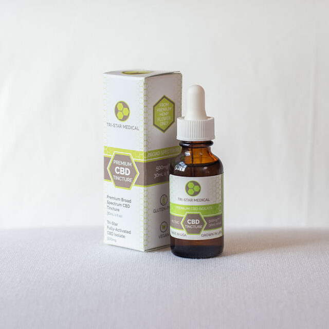 Image of the Broad Spectrum CBD Tincture sitting on a white linen surface in front of a posh bed.