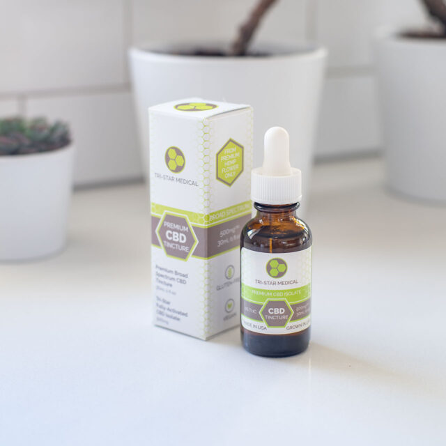 Image of Tri-Star Medical's THC-Free Broad Spectrum Tincture bottle and box on a beautiful white counter in a sunlit kitchen.