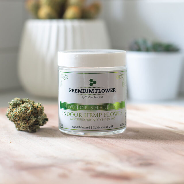Premium Flower by Tri-Star Medical jar with hemp flower on a beautiful wood cutting board in a sun lit kitchen.